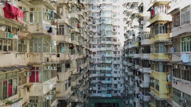 aerial: courtyard surrounded by multiple story high-rise apartments in hong kong - air conditioner stock videos and b-roll footage