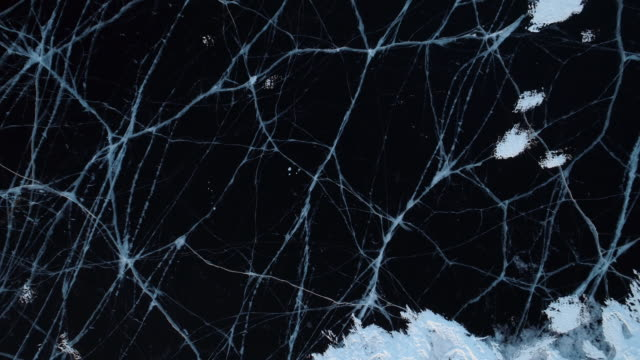 aerial: crack patterns on frozen lake baikal during winter - ice stock-videos und b-roll-filmmaterial