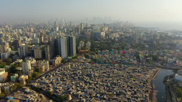 aerial: crowded houses in slum by modern residential buildings and sea - mumbai, india - slum stock-videos und b-roll-filmmaterial