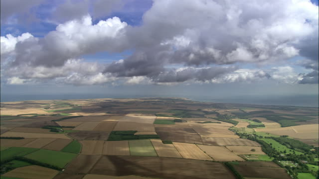 Aerial cumulus clouds casting shadows over cultivated fields / North Yorkshire, England