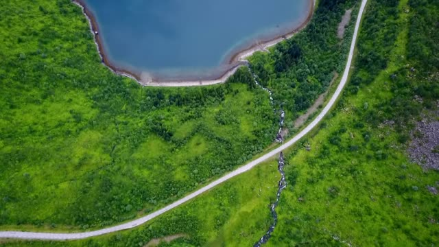 aerial: curvy road crossing stream by beautiful bay - crystal stock videos & royalty-free footage