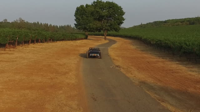 aerial custom hotrod vintage car on country road - classic car stock videos and b-roll footage