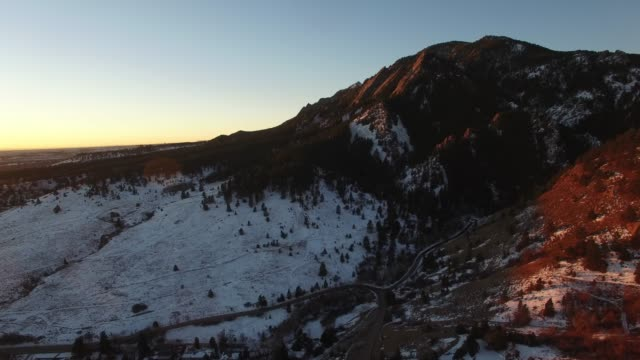 aerial: dark mountains with snow in evening sun - 巨礫点の映像素材/bロール