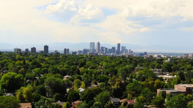 aerial: denver skyline on sunny day over richly forested neighborhoods - denver, colorado - denver stock videos & royalty-free footage