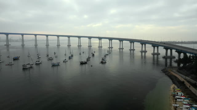 stockvideo's en b-roll-footage met aerial descend: boats floating in ocean water under bridge on cloudy day in san diego, united states of america - san diego