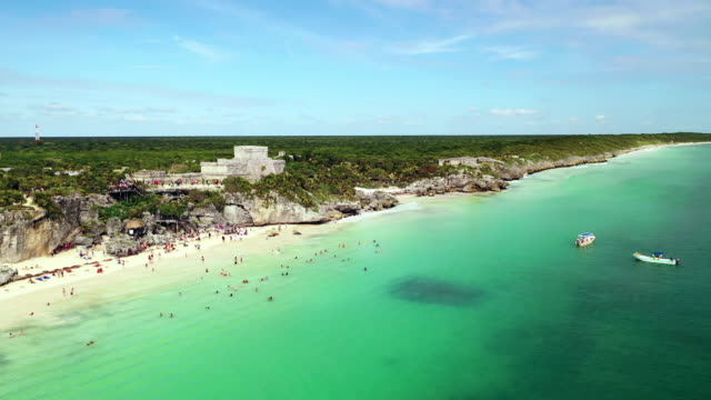 vídeos de stock, filmes e b-roll de aerial descend: crowds in ocean water with beautiful grassy plain behind in tulum, mexico - quintana roo