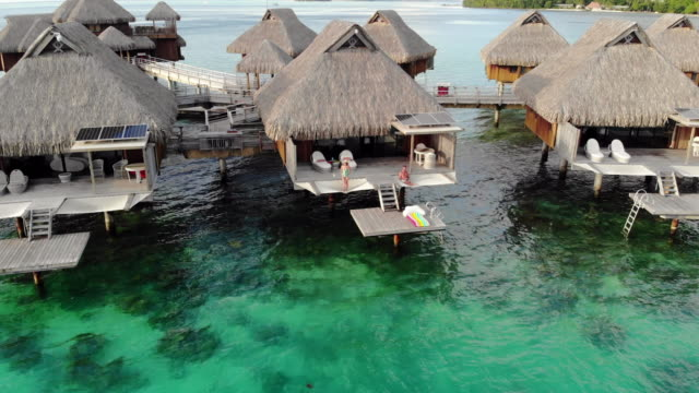 aerial descend: people resting on porch of vacation home in ocean in bora bora, french polynesia - insel tahiti stock-videos und b-roll-filmmaterial