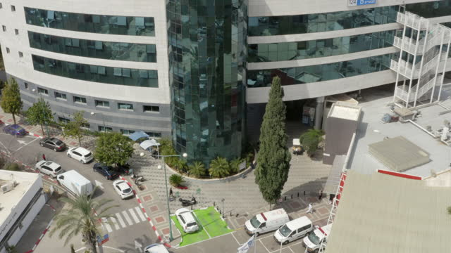 aerial descend shot of people walking in and out of famous hospital on sunny day - tel aviv, israel - israel stock videos & royalty-free footage
