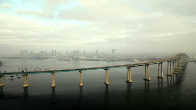 stockvideo's en b-roll-footage met aerial descend: thin bridge leading into city on cloudy day in san diego, united states of america - san diego