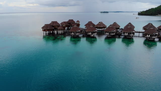 aerial descend: tropical huts in shallow blue ocean water in bora bora, french polynesia - moving down video stock e b–roll