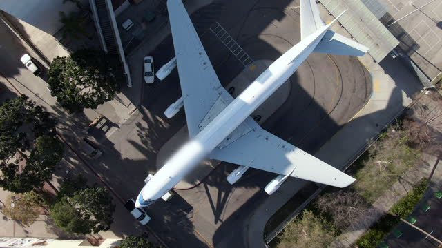 aerial descending and spinning in slow motion to a white airplane proudly on display in an urban setting surrounded by buildings, trees, and a quiet city street - los angeles, california - offbeat stock videos & royalty-free footage