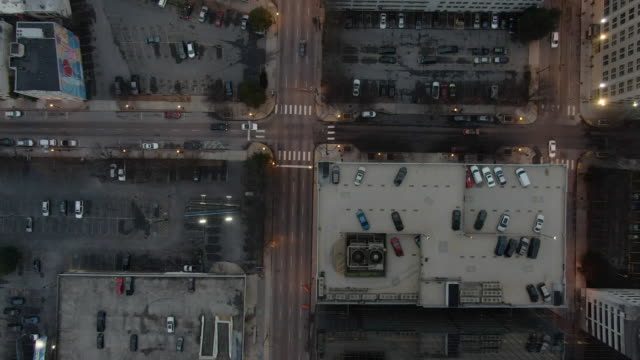 aerial descending: cars drive along streets surrounding parking garages and parking lots at dusk in atlanta - serious stock videos & royalty-free footage