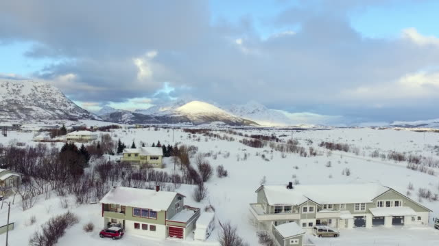 vidéos et rushes de aerial descending: homes covered in white powdery snow in norway - lofoten, norway - chalet