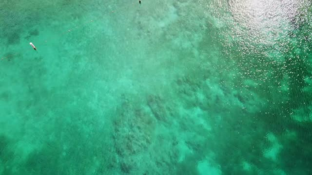 aerial descending: rocky waters of norman island - mar dei caraibi video stock e b–roll