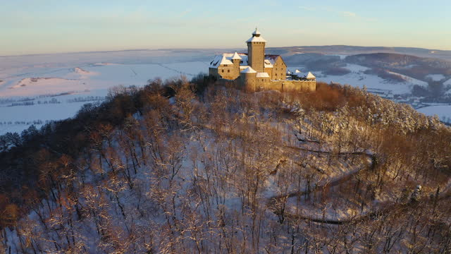aerial descending scenic view of old fortress during winter season, drone flying over trees in forest - thuringia, germany - festung stock-videos und b-roll-filmmaterial