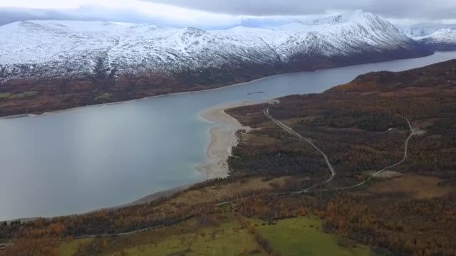 aerial descent: snowy mountains over beautiful lake in autumn in oppdal, norway - pino video stock e b–roll