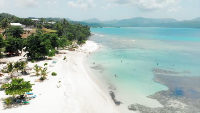 vídeos y material grabado en eventos de stock de aerial descent: stunning tropical beach with mountains in the distance - tumbona