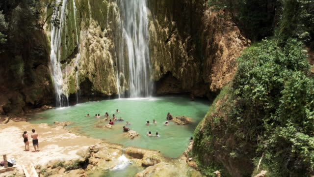 aerial descent: woman jumping into natural pool under picturesque waterfall - ドミニカ共和国点の映像素材/bロール