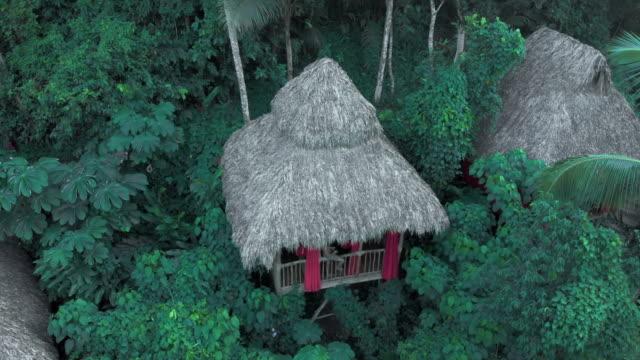 vídeos de stock, filmes e b-roll de aerial descent: young man sitting on balcony balustrade of lovely tree house - treehouse