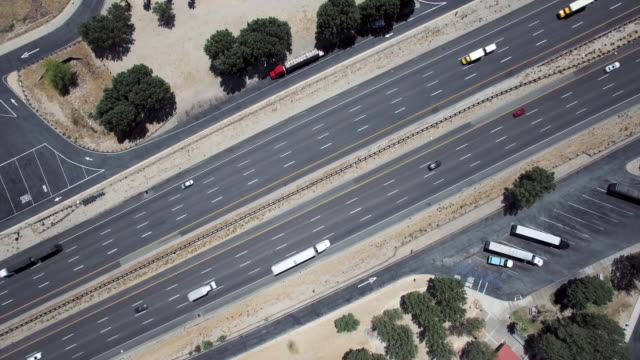 aerial desert freeway overhead cars and trucks passing - 大型トレーラー点の映像素材/bロール