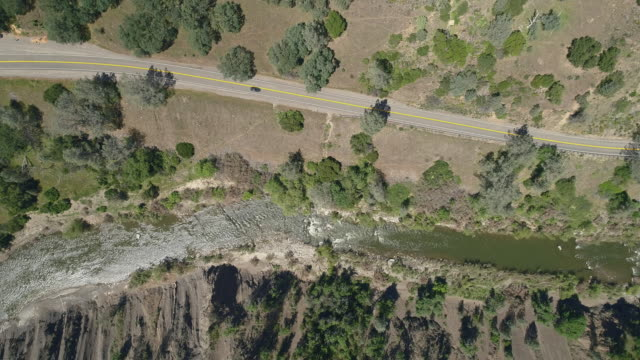 aerial directly above view of a car driving on a highway in cash creek canyon nearby rumsey, california. the sunny spring day.  aerial drone video with the static camera. - canyon stock videos & royalty-free footage