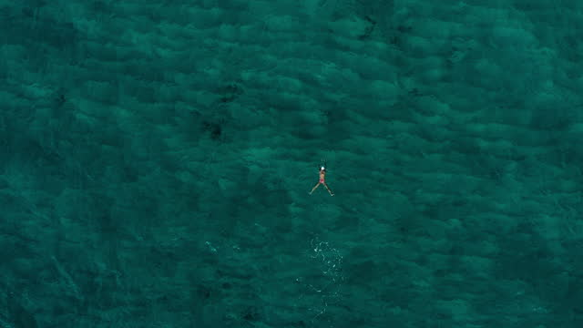 aerial directly over a woman as she swims across rippled ocean water - oahu, hawaii - pacific ocean stock videos & royalty-free footage