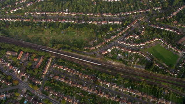 aerial directly over commuter train traveling through suburbs near purley / croydon, south london, england - hd format stock-videos und b-roll-filmmaterial
