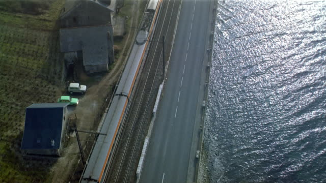 Aerial directly over TGV train traveling along highway on coast / entering tunnel / France