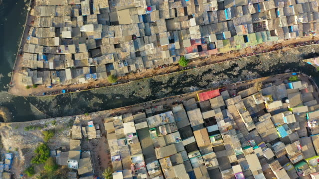 aerial: dirty drainage canal amidst shanties in slum - mumbai, india - slum stock videos & royalty-free footage