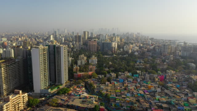 aerial: dirty drainage passing through slum by buildings - mumbai, india - slum stock-videos und b-roll-filmmaterial