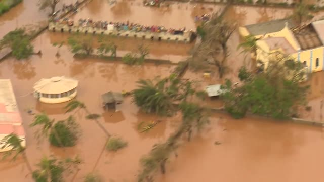 Aerial displaced people sheltering on bridge and on rooves surrounded by flood water after Cyclone Idai in Buzi Mozambique