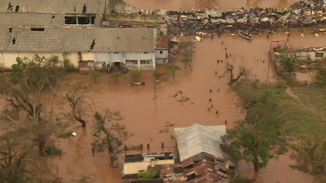aerial displaced people wading through flood water caused by cyclone idai looking for higher ground to shelter on in buzi mozambique - mulinello video stock e b–roll