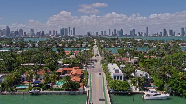 vidéos et rushes de vue aérienne lointaine grand angle du centre-ville de miami le long de venetian way, au-dessus des îles vénitiennes sur une journée venteuse et ensoleillée. clip à basse altitude fabriqué par drone avec mouvement de la caméra de recul. - miami
