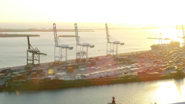 vidéos et rushes de aerial docks shipping container port at sunset florida - biscayne bay