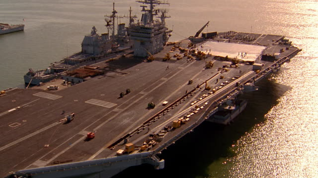 Aerial dolly shot aircraft carrier and battleship docked in harbor / Norfolk, Virginia