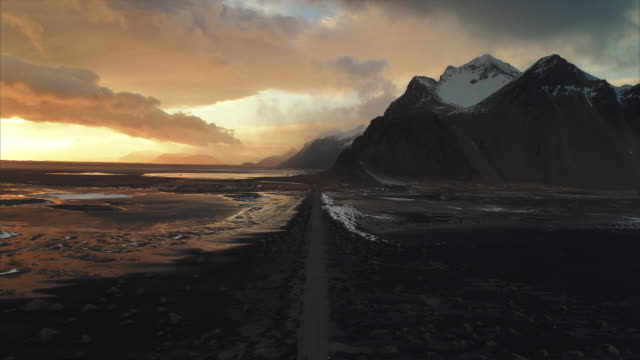 vídeos y material grabado en eventos de stock de aerial dolly shot at sunset showing vestrahorn mountain on the stokksnes peninsula, iceland - terreno extremo