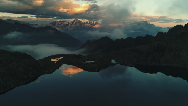 vídeos de stock e filmes b-roll de aerial dolly shot showing a high altitude lake and dramatic mountain landscapes at sunset, dolomites, italy - contraste