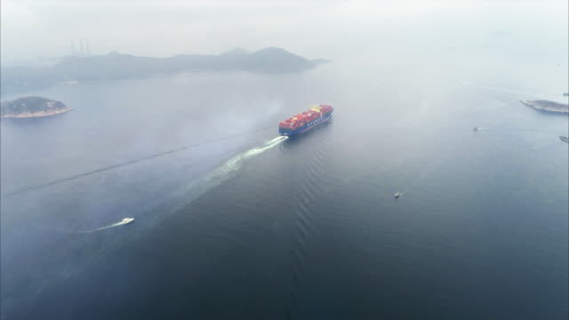 aerial dolly shot showing a large container ship sailing towards the ocean, hong kong - cargo ship stock videos & royalty-free footage