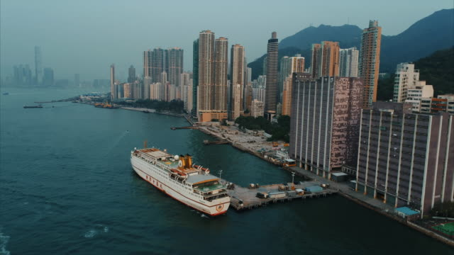 vídeos de stock e filmes b-roll de aerial dolly shot showing a ship moored next to various skyscrapers, hong kong island, hong kong - embarcação comercial