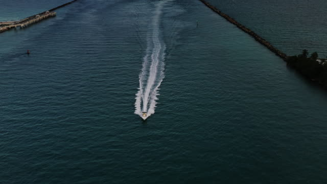 aerial dolly shot showing a speedboat heading down a sea channel, miami, florida, united states of america - miami dade county stock videos & royalty-free footage