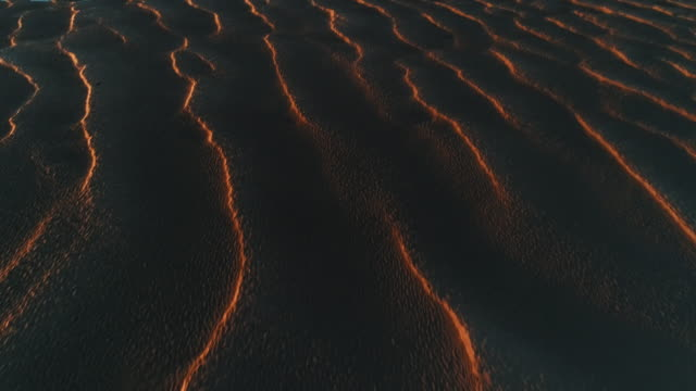 aerial dolly shot showing evening light catching sand patterns at low tide, borth-y-gest, wales, united kingdom - tilt down stock videos & royalty-free footage
