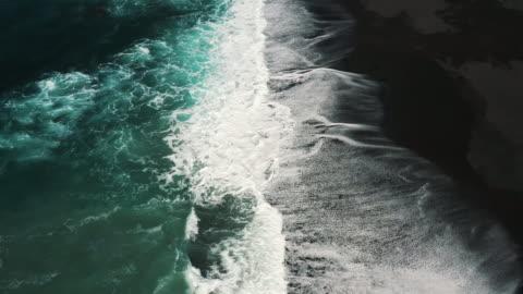 vídeos de stock, filmes e b-roll de aerial dolly shot showing waves crashing onto a black sand beach, lanzarote, spain - oceano atlântico