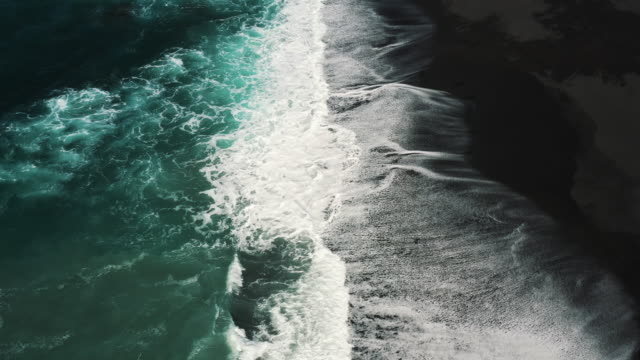 aerial dolly shot showing waves crashing onto a black sand beach, lanzarote, spain - contrasts stock videos & royalty-free footage