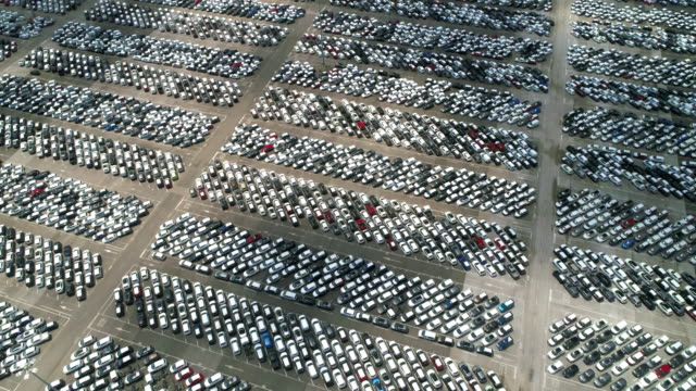 aerial dolly shot tilting down to show a large number of new cars, livorno, italy - parallele geometrie stock-videos und b-roll-filmmaterial