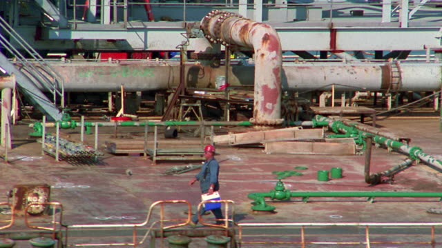 aerial dolly shot zoom out from man walking on deck to wide shot cargo ship docked in industrial harbor / houston, texas - porto marittimo video stock e b–roll