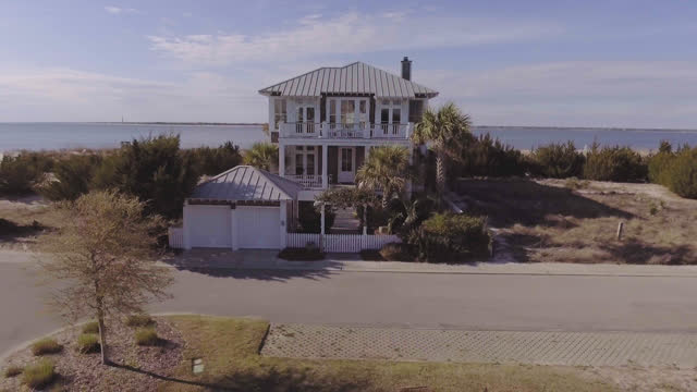 drone. aerial dolly-out from front steps of luxury two-story seaside beach house to overhead view on sunny summer day. - beach house stock videos & royalty-free footage
