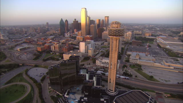 Aerial WS Downtown buildings reflecting afternoon sun with Reunion Tower in foreground / Dallas, Texas, USA