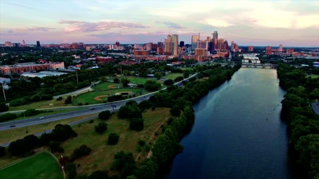 stockvideo's en b-roll-footage met antenne: dramatische zonsondergang flying over dorp lake richting centrum van austin, texas vanuit west view - capital cities
