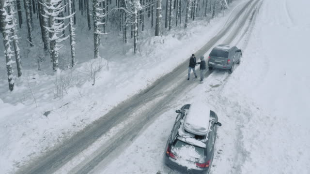 Aerial Driver stopping to help man stuck in snow
