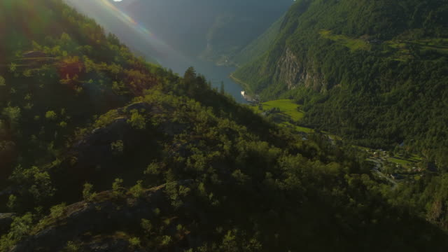 aerial: drone approaching geirangerfjord amidst majestic green mountains - geiranger fjord, norway - inlet stock videos & royalty-free footage